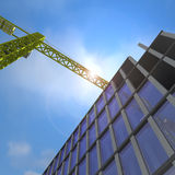 Crane Over Building. A crane over a building with added sunflare Royalty Free Stock Images