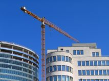Crane over modern buildings. A crane between two modern buildings in downtown Brussels, near the Brussels Central railway station royalty free stock image