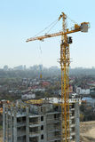 Crane over new boulding. Building crane and building under construction against blue sky Stock Image