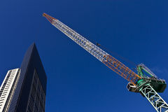 Crane over skyscraper Stock Photos