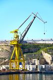 Crane in Paola docks, Malta. Industrial crane in the docks with buildings to the rear, Paola, Malta, Europe Royalty Free Stock Photography