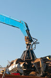 Crane picking up metal waste. Blue crane picking up metal waste Royalty Free Stock Image