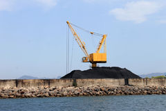 Crane and pile of coal on docks Royalty Free Stock Images