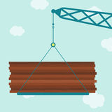 Crane with plywood wood. Crane carrying a plywood wood stack. Blue sky in the background Stock Photo