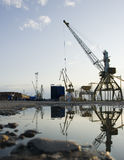 The crane at the port. The crane in the river port with the reflection in the water in the foreground Stock Photography