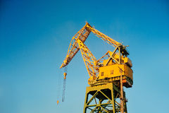 A crane at a port painted in yellow Stock Images
