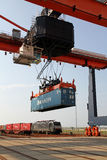 Crane on rails lifting containers Stock Images