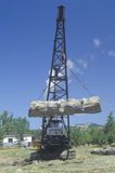 A crane raising a weathered log as part of a reenactment of the workings of a 19th century lumber mill Royalty Free Stock Photo