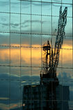 Crane reflected. Building crane at sunset reflected in tower windows Stock Image