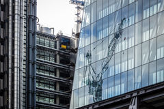 Crane reflection. A reflection of a crane in the glazed facade of the Leadenhall building with Lloyds bank in the background Stock Photos