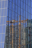 Crane reflection in a skyscraper. Slewing crane reflecting in glass wall of an office building Royalty Free Stock Photography