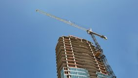 A crane rissing above a new high rise building under construction. stock photos