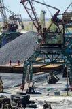 Crane in river port. Heavy cranes unloading metal to import. Steel delivery Stock Photo