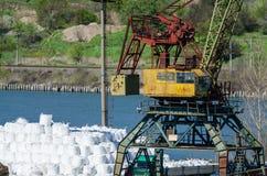 Crane in river port. Heavy cranes unloading metal to import. Steel delivery Stock Photos