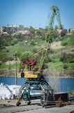 Crane in river port. Heavy cranes unloading metal to import. Steel delivery Royalty Free Stock Photography
