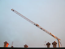 Crane. A crane on a roof with chimneys Royalty Free Stock Photos