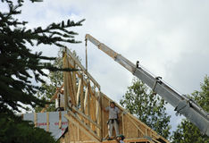 Crane for roof framing with workers Stock Image