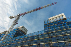 Crane and Scaffolding on a new building. With blue safety screen. Copyspace Stock Photography