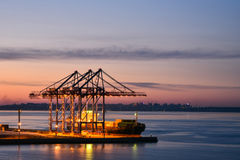 Crane and ship in night sea port. Royalty Free Stock Image
