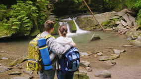 Crane shot: A couple of tourists with backpacks admire the beautiful waterfall and the mountain river. Back view