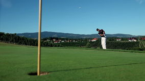 Crane shot of a man golfer that hits a white golf ball with a golf club and the stock video