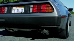 Crane shot of outatime license plate to delorean driving down road stock video footage
