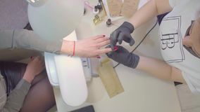 Manicurist applies cuticle oil to the nails of the client stock footage