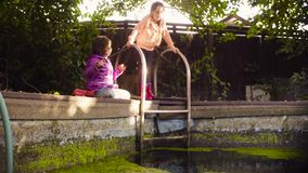 Two girls playing near the old pool overgrown with duckweed. Crane shot. Two girls playing near the old pool overgrown with duckweed. A girl catching orange stock video