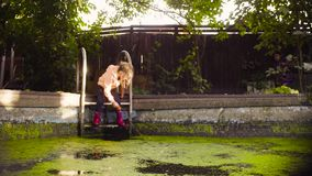 Two girls playing near the old pool overgrown with duckweed. Crane shot. Two girls playing near the old pool overgrown with duckweed. A girl taking off orange stock footage