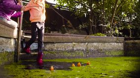 Two girls playing near the old pool overgrown with duckweed. Crane shot. Two girls playing near the old pool overgrown with duckweed. They putting there orange stock footage