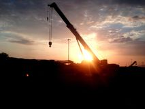 Crane silhouette at construction site royalty free stock image