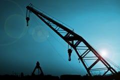 Crane. Silhouette over blue sky and lens flair Stock Photos
