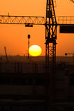 Crane silhouette over sun under construction Stock Images