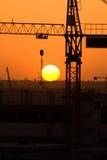 Crane silhouette over sun under construction. Symbol Stock Images