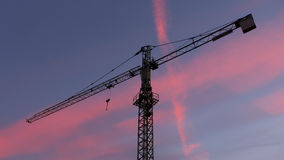 Crane silhouette at sunset. Crane with beautifl pink clouds at sunset Stock Image
