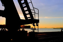 Crane silhouette at sunset in the port Stock Images