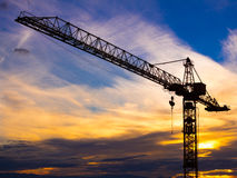 Crane silhouetted against the sunset with orange clouds Royalty Free Stock Image