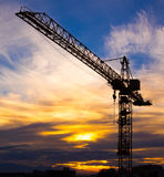 Crane silhouetted against the sunset with orange clouds Royalty Free Stock Photo