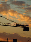 Crane silhouetted at sunset. Scenic view of arm of crane in urban area silhouetted with sunset and cloudscape background royalty free stock photos