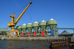 Crane and silos of a gravel plant on a pier Royalty Free Stock Photo