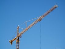 Crane in the sky. A very large yellow crane against a clear blue sky Royalty Free Stock Images