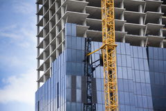 Crane on skyscraper construction site with windows reflecting sky Royalty Free Stock Images