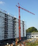 A crane stands in front of a building Royalty Free Stock Photo