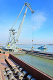 Crane and steel plate in harbor Royalty Free Stock Image