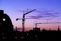 Crane su un cantiere alla notte alla notte Fotografie Stock