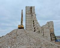Crane su un mucchio di rubish accanto ad una torre giù spogliata dell'appartamento demolita metà Fotografia Stock