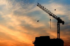 Crane and sunrise. Beautiful sky at sunrise in city. Building under construction and crane Stock Photos