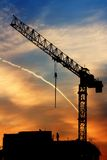 Crane and sunrise. Beautiful sky at sunrise in city. Building under construction and crane. Also trace from airplane in sky and two workers at top of the Royalty Free Stock Photography