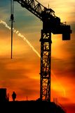 Crane and sunrise. Beautiful sky at sunrise in city. Building under construction and crane. Also trace from airplane in sky and worker at top of the building Royalty Free Stock Image