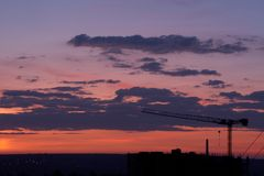 Crane in the sunset sky. Crane erecting a building in the sunset skies over the city Stock Photo